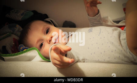 Portrait Of Baby Boy Pointing While Lying On Bed Banque D'Images