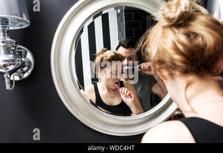 Réflexion de couple se brosser les dents vu en miroir d'une salle de bains privative Banque D'Images