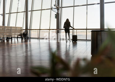 Woman with suitcase in airport Banque D'Images