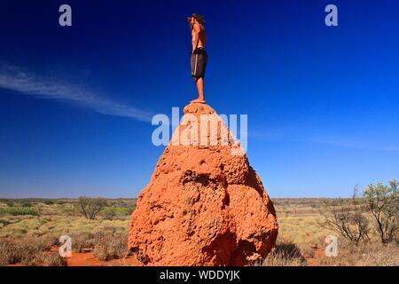 L'homme torse nu debout sur Rock sur le terrain contre le ciel Banque D'Images