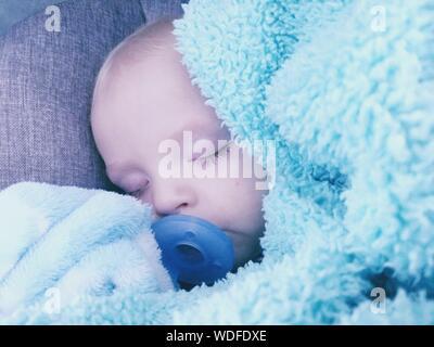 Close-up of Baby Boy Sucking Pacifier tout en dormant sur le lit Banque D'Images