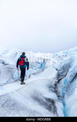 Vue arrière pleine longueur de l'homme marche sur glacier Against Sky Banque D'Images