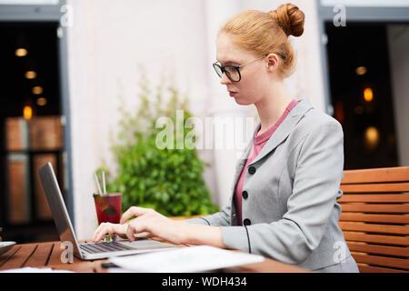 Jeune femme sérieuse se concentrant sur son travail en ligne elle assise à la table et de la saisie sur ordinateur portable en café-restaurant en plein air