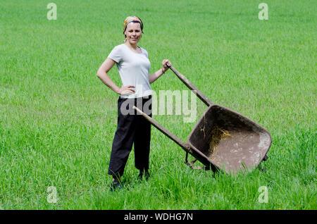 Portrait of smiling Woman with Hand On Hip et brouette debout sur Farm Banque D'Images