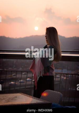 Vue de côté de femme enveloppée dans un châle en fustigeant Sky pendant le coucher du soleil Banque D'Images