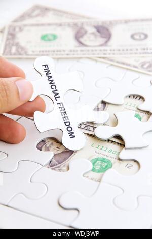 Close-up of Hand Holding Jigsaw Piece sur devises papier Banque D'Images