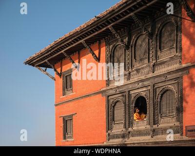 Sadhu saint homme assis dans la fenêtre de lecture, à Ancient Hindu Mandir népalais, dédié au Dieu Shiva, Varanasi, Uttar Pradesh, Inde, Asie Banque D'Images