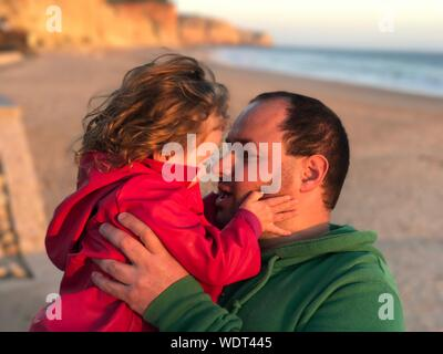 Mid adult Man Lifting Daughter At Beach Banque D'Images