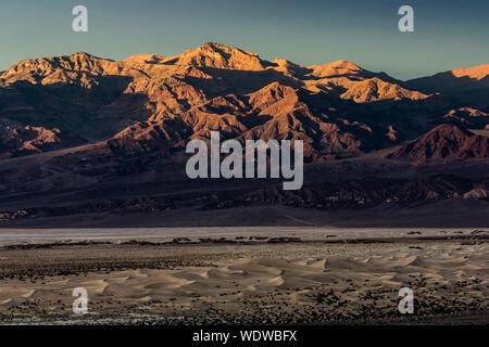 Le coucher du soleil illuminant dé à pic dans la Death Valley National Park avec Mesquite Sand Dunes en premier plan Banque D'Images