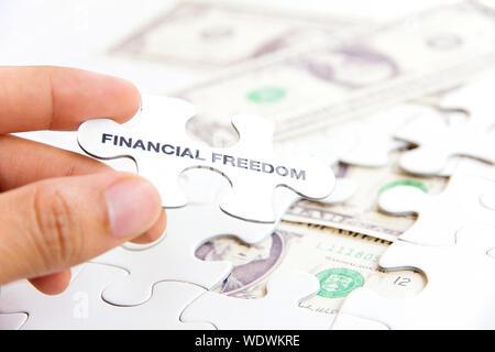 Cropped Hand Holding Jigsaw Piece sur du papier-monnaie Banque D'Images