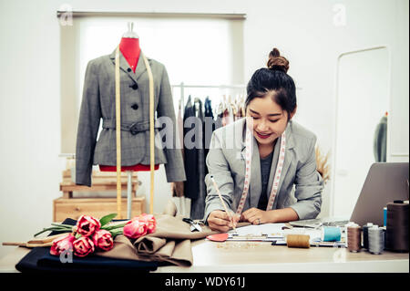 Jolie Asian female fashion designer working in home office atelier. Fashionista élégant chiffon femme créant de nouveaux design collection. Et sur mesure Banque D'Images