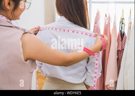 La mesure de couturière female customer épaule dans l'atelier de couture atelier bureau. Créateur de mode sur mesure et concept. Offres et demandes d'emploi et de profession. Bu Banque D'Images