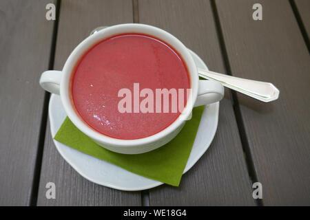 Portrait de soupe de betteraves dans un plat de service sur table en bois Banque D'Images