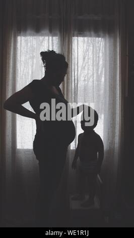 Silhouette garçon debout par mère enceinte contre fenêtre à Accueil Banque D'Images