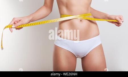 Portrait de Jeune femme tenant un ruban à mesurer autour de taille contre fond blanc Banque D'Images