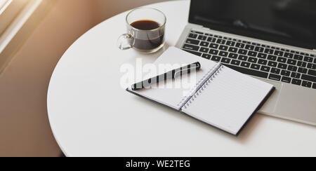 Ordinateur portable ouvert avec les fournitures de bureau sur une table en bois blanc dans Poste de travail confortable Banque D'Images
