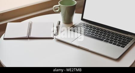 Portrait d'un minimum de travail avec ordinateur portable écran vide ouvert, ouvrez Ordinateur portable et une tasse de café Banque D'Images