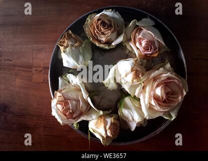 Tourné directement au-dessus des Roses fanées dans le récipient sur la table Banque D'Images