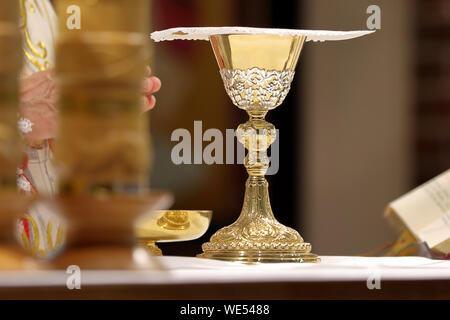 Calice à l'autel et Prêtre célébrer la messe