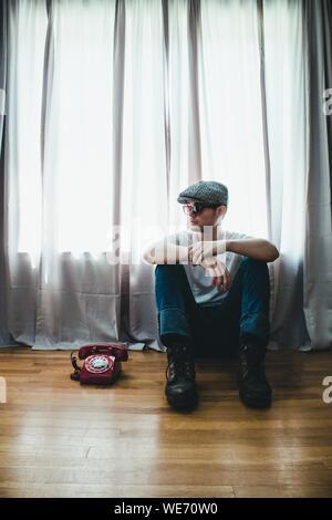 Jeune homme assis par téléphone à cadran sur plancher de bois franc à la maison Banque D'Images