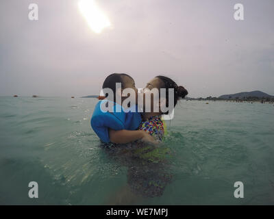 Vue latérale du Mother Kissing fils tandis que la natation en mer contre Ciel nuageux Banque D'Images