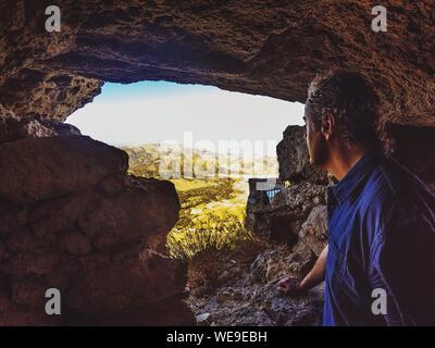Vue de côté de l'homme à la montagne tout en se tenant à moins de Rock Formation Banque D'Images