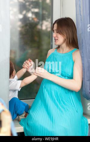 Femme enceinte et son fils assis sur le rebord de fenêtre Banque D'Images