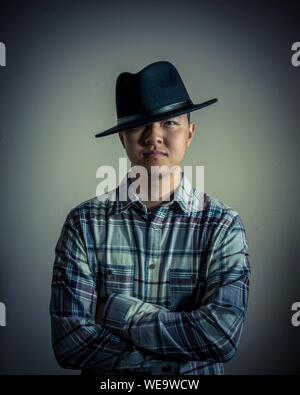 Portrait Of Man Wearing Hat contre l'arrière-plan gris Banque D'Images