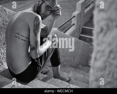 High Angle Portrait de jeune homme tatoué Sitting on Steps Banque D'Images