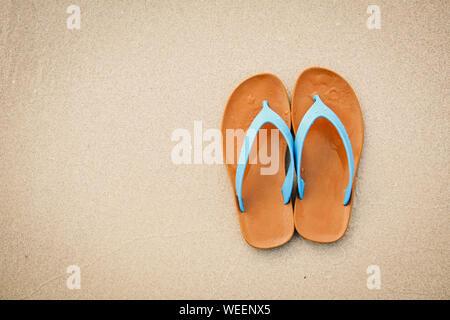 Close-up of Orange flip-flops sur Sand At Beach Banque D'Images
