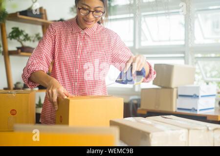 Jeune femme Coller du ruban adhésif sur boîte en carton à la maison