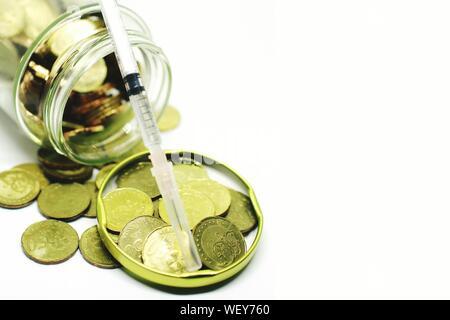 Close Up of Coins avec seringue Against White Background Banque D'Images