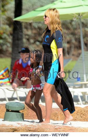Paradise Island, Bahamas - Top Model Heidi Klum maman continue sa maison de vacances avec ses enfants Leni, Henry, Johan et Lou Sulola visite et Baie des Dauphins. Heidi et les enfants ont revêtu des combinaisons pour entrer dans l'eau avec tous les autres jeunes et les membres de la famille. Heidi a dû partir brusquement à ce qui semblait traiter quelques affaires sur son téléphone et transformé en deux pièces bikini à regarder à partir de la rive. Après l'expérience dolphin Heidi est allé pour une promenade de plage avec sa fille Leni avant le coucher du soleil pour la soirée. AKM-GSI 26 Mars, 2014 Banque D'Images