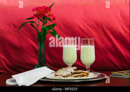 Deux verres de lait et de fleurs au pied d'un lit dans un hôtel de luxe chambre. Banque D'Images