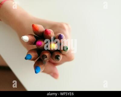 Cropped Hand Holding des crayons sur la table Banque D'Images
