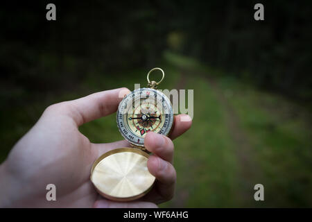 Cropped Hand Holding Compass In Forest Banque D'Images