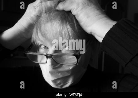 Close-up Portrait of Senior Woman with Hand in Hair portant masque la pollution sur fond noir Banque D'Images