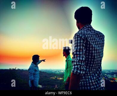 Vue arrière de l'homme Photographie Amis sur Mountain au coucher du soleil Banque D'Images