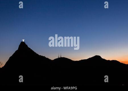Vue éloignée du Christ Rédempteur statue sur Silhouette contre la montagne ciel clair au crépuscule Banque D'Images