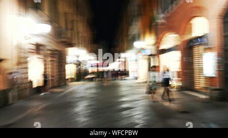 Blurred Motion de personnes marchant sur la rue au milieu d'édifices illuminés Banque D'Images