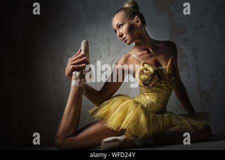 Ballerine magnifique qui s'étend alors qu'il était assis contre le mur dans le noir Banque D'Images