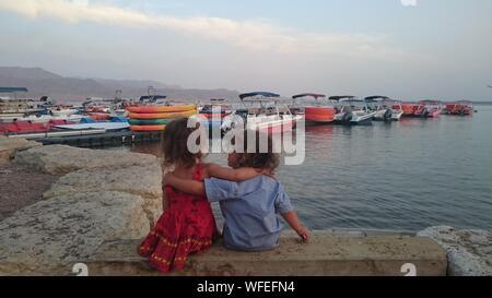 Vue arrière de la fratrie avec les bras autour d'un mur de soutènement sur bateaux contre Banque D'Images