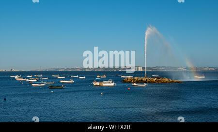 Formant un geyser sur arc-en-Tage avec les bateaux de pêche surplombant 25 avril Bridge et la statue de Cristo Rei à Lisbonne, Portugal with copy space Banque D'Images