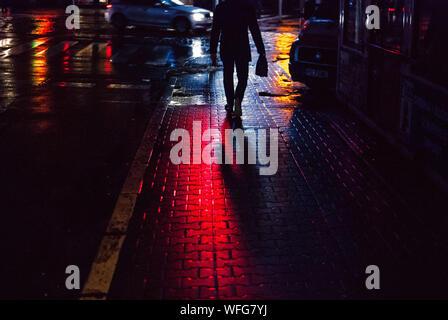 La section basse Silhouette de l'homme marchant sur un trottoir mouillé dans la nuit Banque D'Images