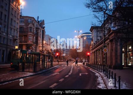 Les gens qui marchent sur la ville illuminée à la tombée de la rue Banque D'Images