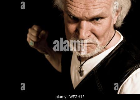 Portrait de Angry Man Clenching Fist sur fond noir Banque D'Images