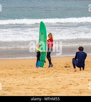Père de prendre une photo de la mère et de son holding a surfboard vert à Manly Beach Sydney NSW Australie. Banque D'Images
