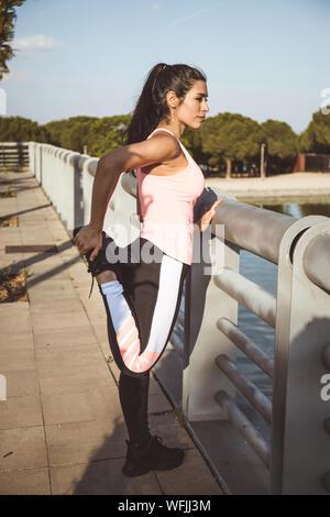 Femme latine n'étirement musculaire en face d'un lac et vêtue de rose top et pantalon noir Banque D'Images