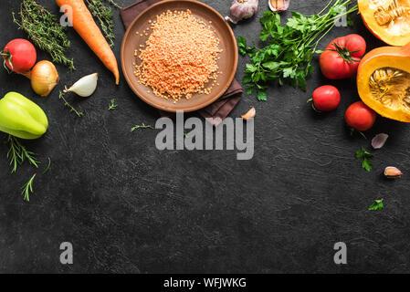 Automne fond de cuisson de lentilles rouges, avec des légumes biologiques de saison sur noir table de pierre, vue du dessus, copiez l'espace. Ingrédients pour la soupe de saison automne Banque D'Images