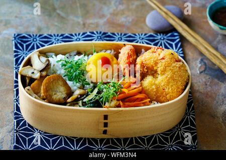 Boîte bento japonais avec tempura de gambas, riz et légumes Banque D'Images